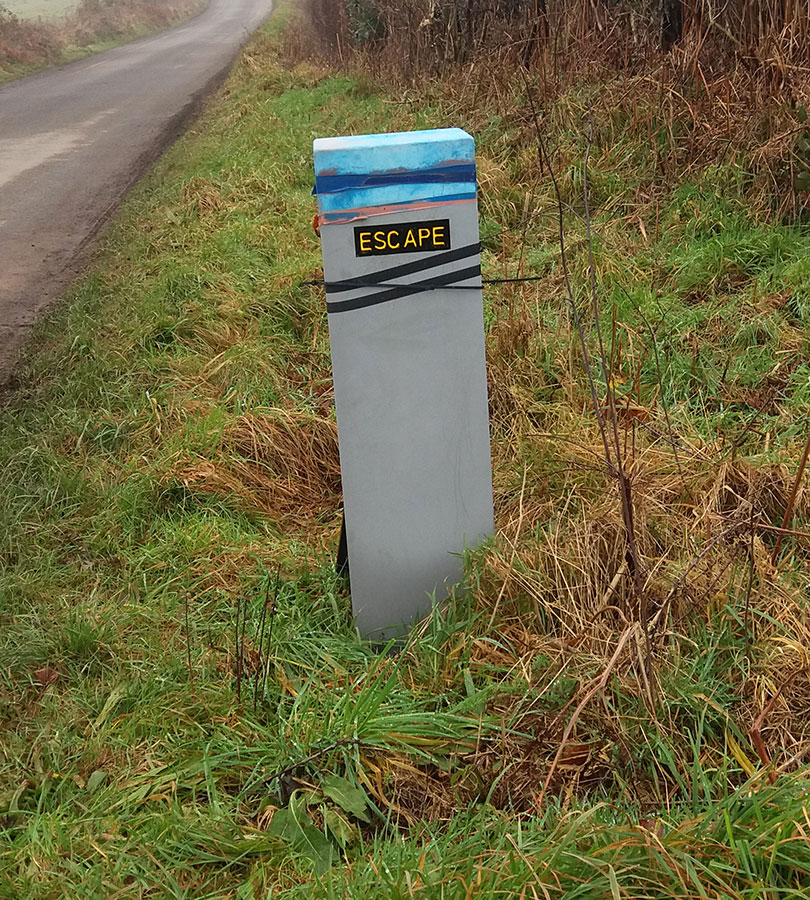A concrete bollard by the road has a sign attached which reads, 'escape'.