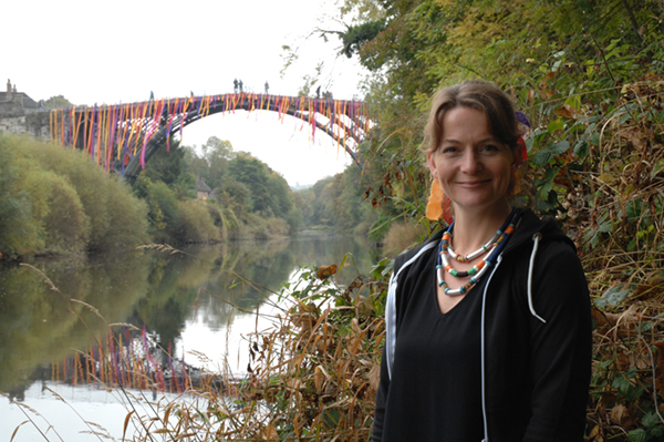 Artist Faye Claridge in front of the Iron Bridge during the Weighty Friend event.