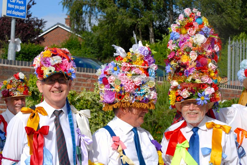 Three men in shirts and ties decorated with bright ribbons wear hats that host towers of bright flowers
