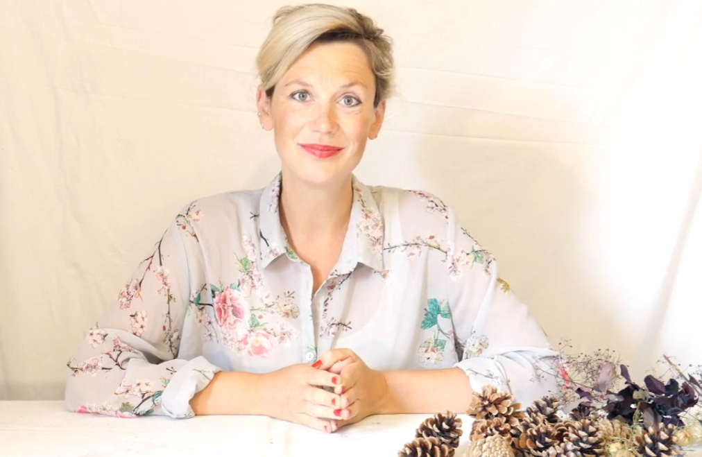 A blonde woman sits behind a pine-cone covered desk, she is smiling