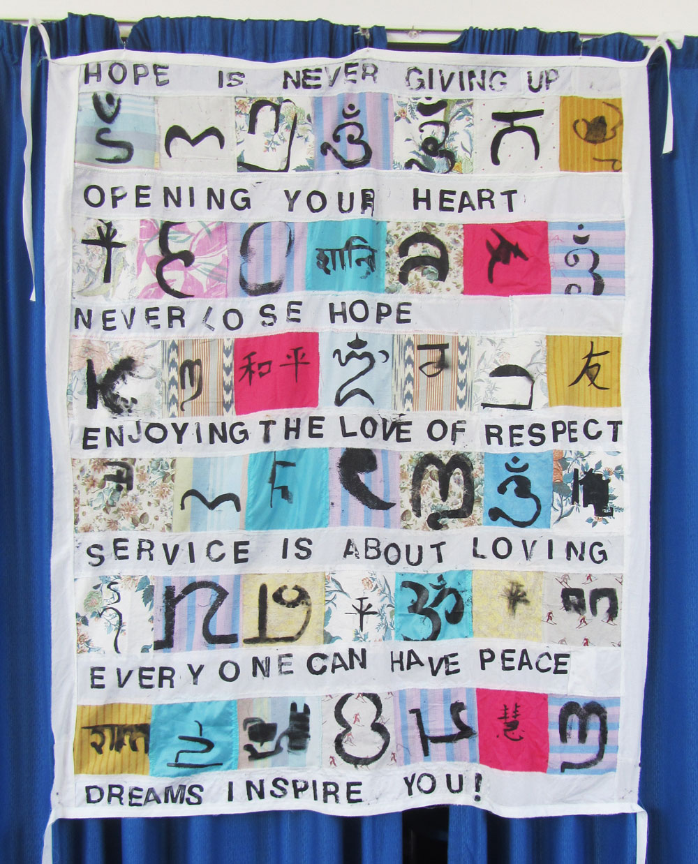 A textile hanging, featuring pictorial squares of text artwork and longer strips of text phrases.