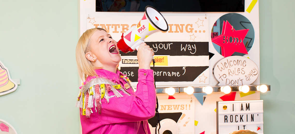 A blonde woman in a bright pink jumpsuit speaks into a megaphone