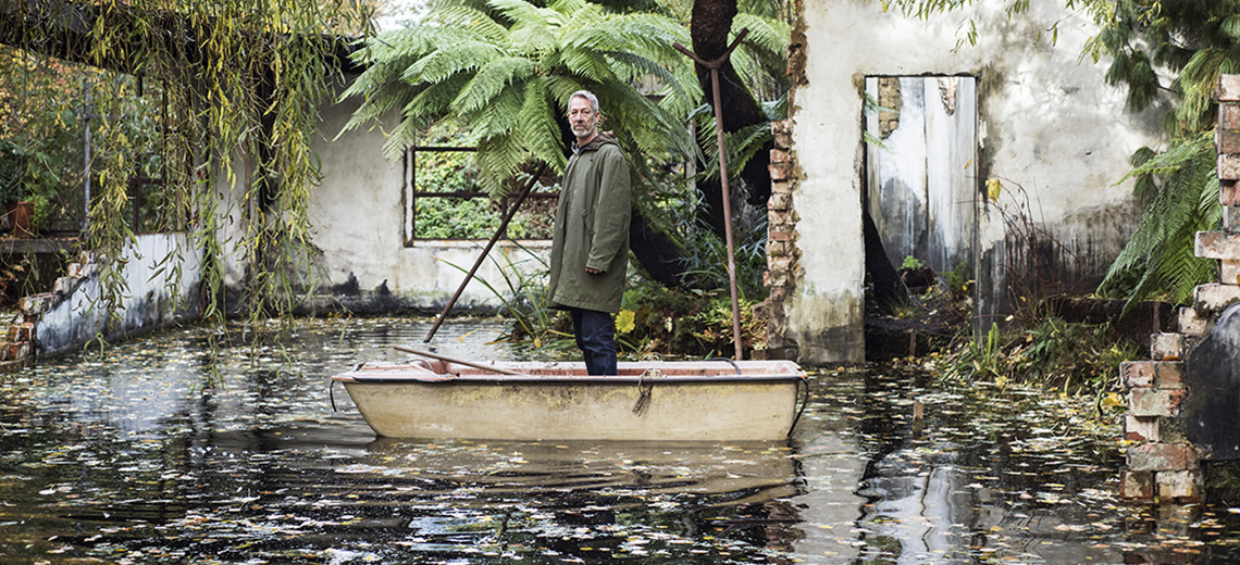 A man stands in a rowing boat in an installation that looks like a ruined and flooded building